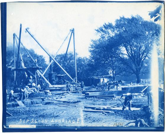 Blue-tinted photograph of people working at a construction site.