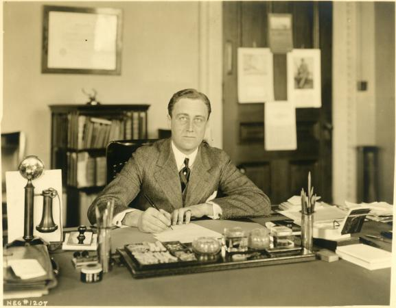 Franklin Delano Roosevelt sitting at his desk in the Executive building.
