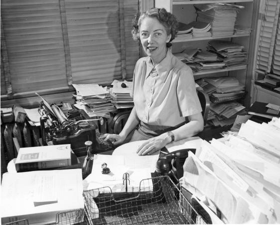 A woman sits at a desk near a typewriter and many stacks of papers.