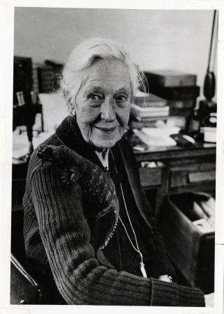 Black and white photographic portrait of an elderly woman seated at her work desk. Books can be seen
