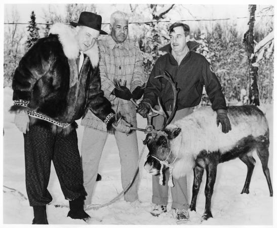 Three men stand in the snow with a reindeer.