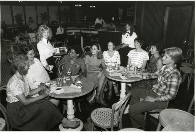 Two waitresses serve ice cream to a group of young adults.