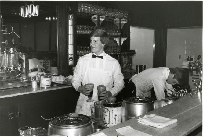 Two men stand behind a counter. One man is holding an ice cream float in each hand.