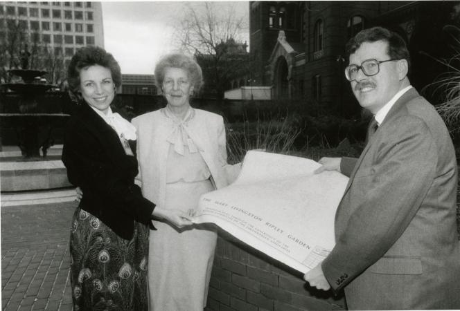 "Two women and one man hold up a large piece of paper that reads: ""The Mary Livingston Ripley Garden."