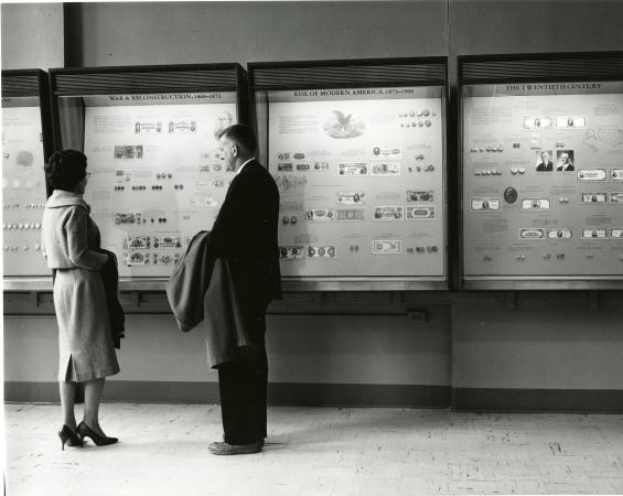 A man and woman stand in front of four exhibit cases of coins and paper currency.
