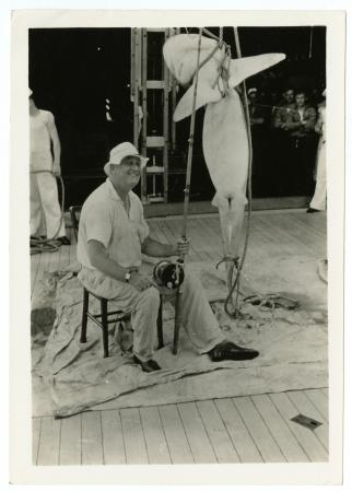 President Roosevelt sitting on a stool, leisurely dressed holding a fishing rod next to his large ca