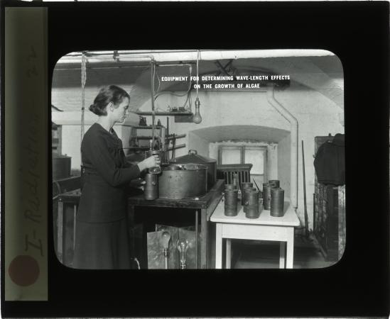 A person stands in a room with scientific instruments. She appears to be working on an experiment.