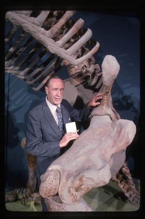 A man in a suit stands next to skeletal bones that are much larger than him.