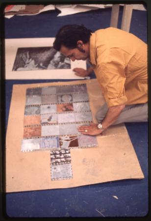 A man leans over toward patterned prints on a large document.