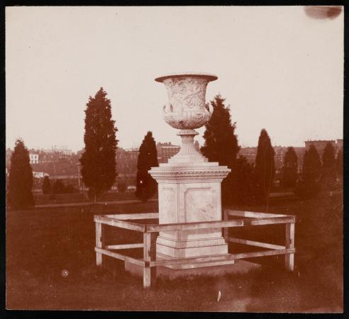 An urn sits in a grassy area. It sits on a pedestal. The base is surrounded by a wood fence.