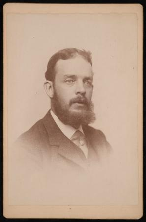 Portrait of a man wearing a suit with a beard.