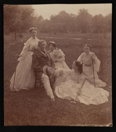 Henry and four women sit and pose in a field.