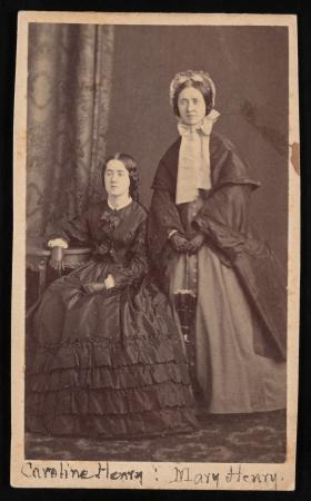 Caroline Henry is seated and Mary Henry stands behind her. Both women are wearing long dresses and n