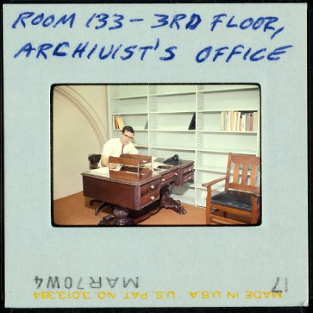 A photo slide of a man sitting at a desk.