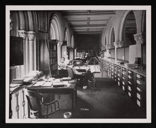 Office space with one man working at the second desk closest to the camera. Books are on the desks.