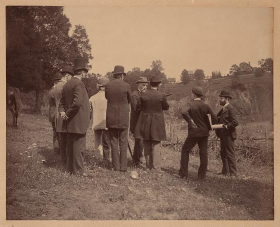 Men wearing suits stand in an open field.