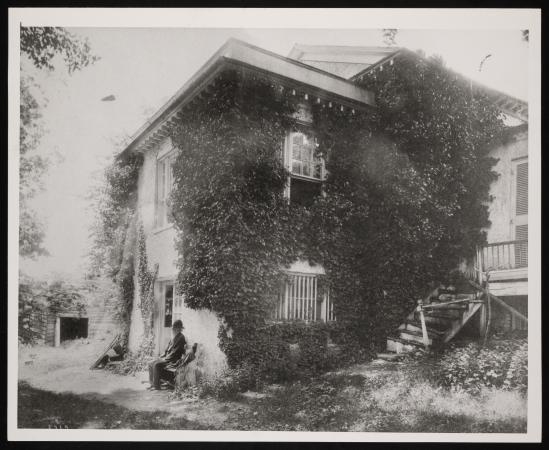 A man sits outside on a bench in front of Holt House. Overgrown greens cover the building.