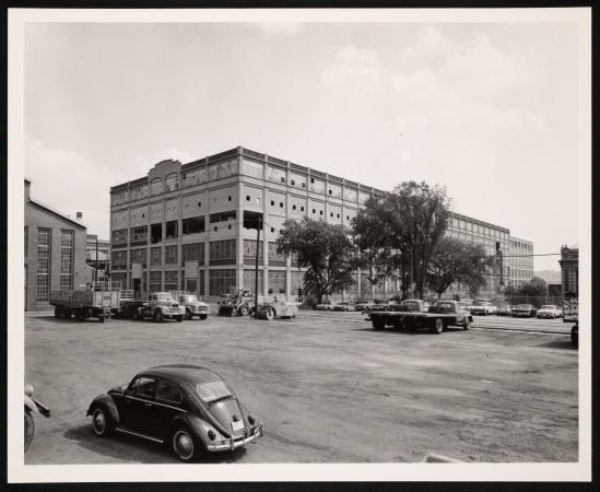 Exterior view of a building. 1960s cars are parked in the streets.