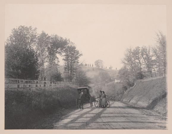 Two people sharing a bicycle stop near a horse and carriage on a dirt road.