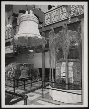 View of a corner of an exhibit that features a bell and a wagon.