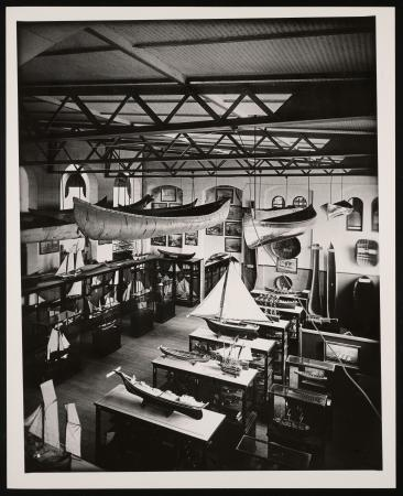 In a large hall, ship models are exhibited in and on top of exhibit case and canoes hang from the ce