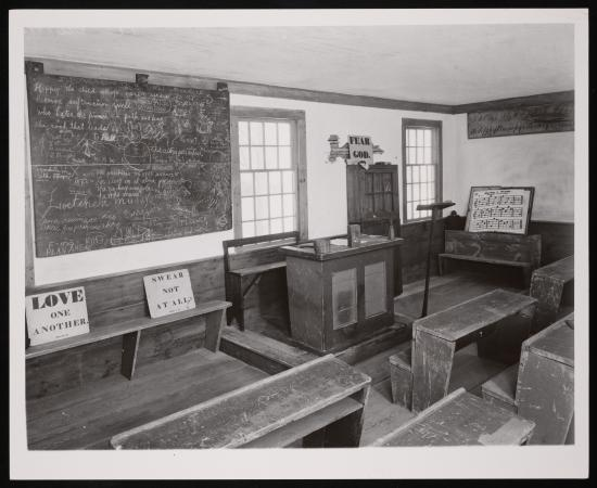 A scene of a New England schoolroom.