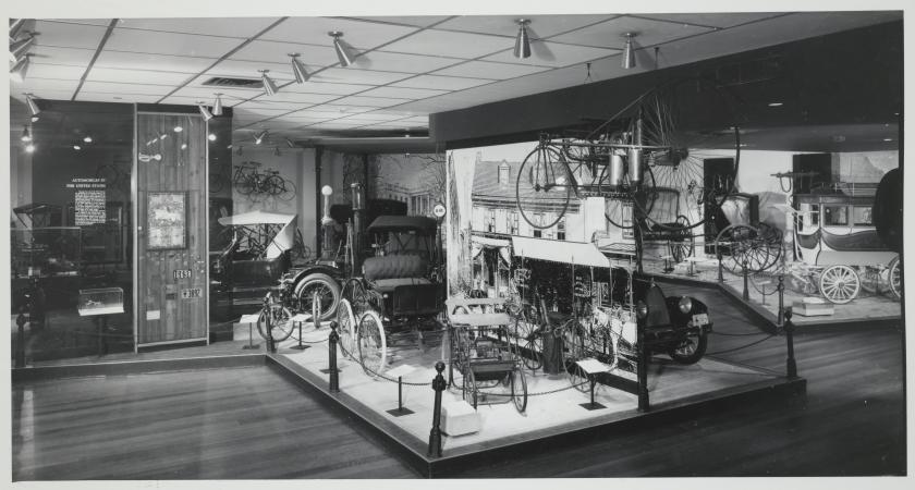 Carriages, automobiles, and cycles on display in an exhibit hall.