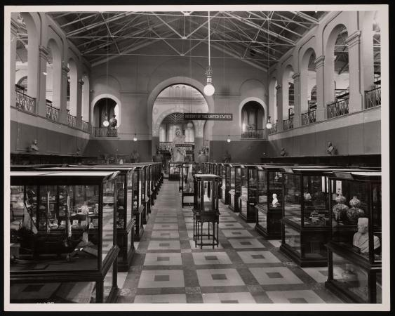 Exhibit cases In a large hall. A hanging sign reads: