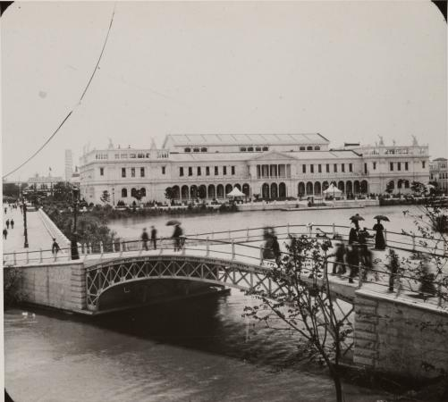 People walk across a bridge. The Woman's Building is in the background.