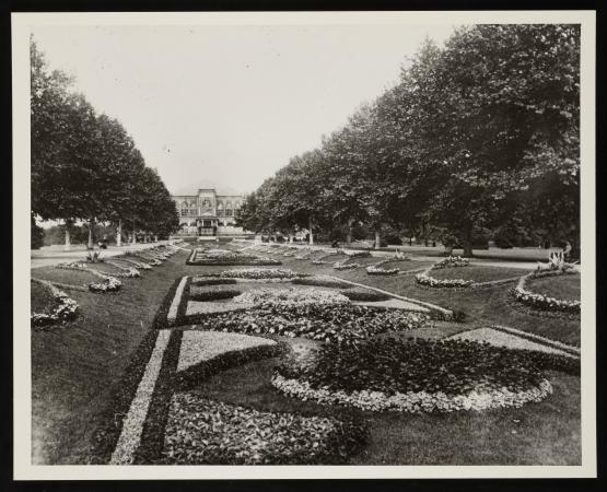 View of the sunken garden with pathways. Tall trees are on either side of the garden patterns. A vie