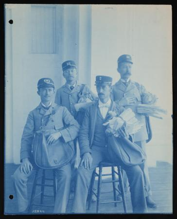 Four men in postal service uniforms pose for a photo. Two are seated. Because this is a cyanotype, t
