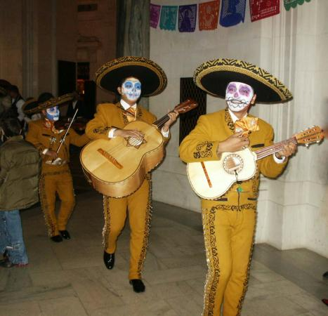 Three men in mariachi outfits hold instruments and walk. They are wearing hats and their faces are p
