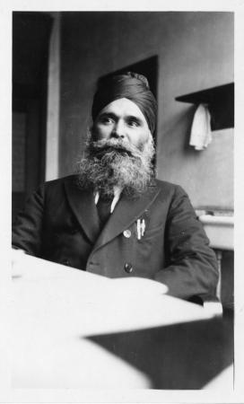 A person wearing a suit and a head wrap sits at a desk. He has two pens in his front pocket.