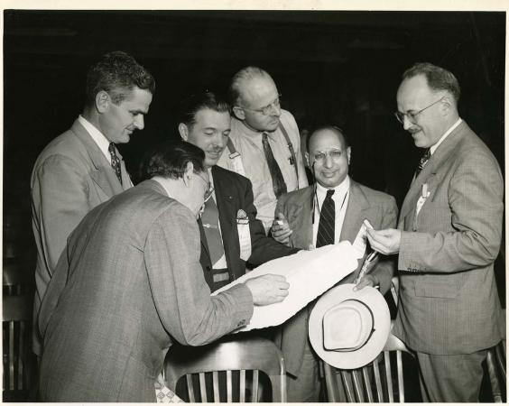 Six men in suits huddle around a square, flat object. One man looks directly at the camera.