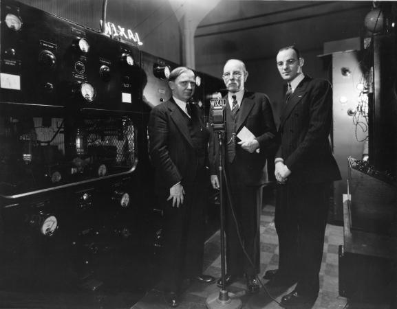 Three men in suits standing behind a microphone and in front of a wall of speakers and meters.