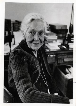 A portrait of Doris Holmes Blake looking at the camera with a faint smile. Her pet lizard sits on he
