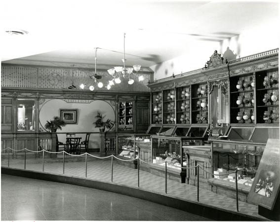 Image of a counter with shelves and glass counters. It is roped off.
