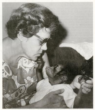 A woman holds a small primate in a white shirt.