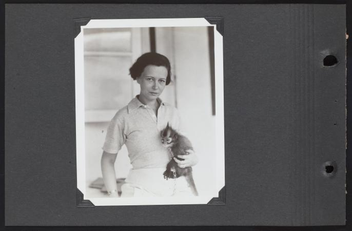 Lucile Mann stares directly into a camera and holds a monkey.