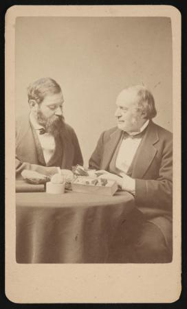 Two men sit at a table together. One is looking at the other and grinning. Rocks appear to be on the