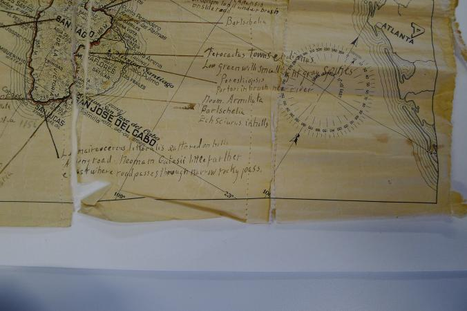 A small portion of a printed map is shown atop a piece of white blotter. Folds and tears interrupt t