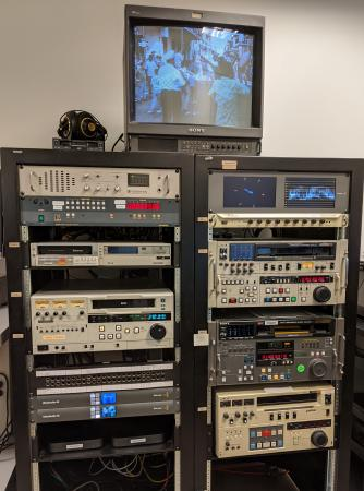 A rack of assorted legacy video decks. A monitor sitting on top of the rack shows a screenshot of a