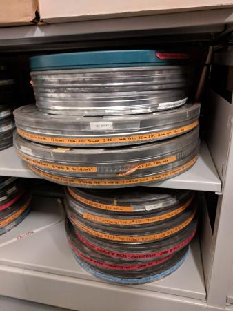 Circular tin cans for film that are stacked on top of one another. Slight rust is visible,