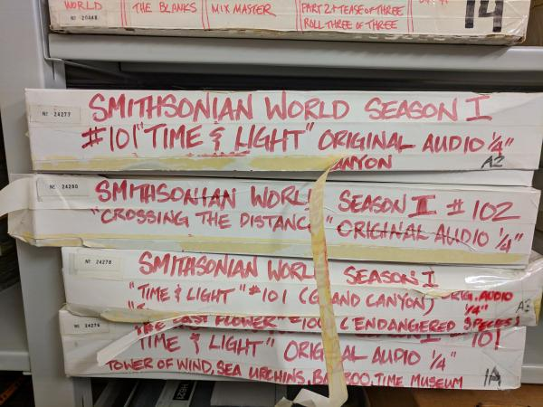 "Long, thin cardboard boxes labeled ""Smithsonian World"" with various episode titles. The boxes are st"