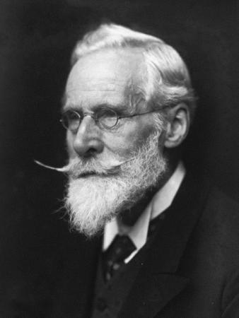 Close-up portrait photograph of a man with white/gray hair and a long mustache and beard. The man is
