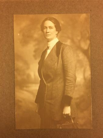 A photograph of a woman in a tweed suit standing and looking at the camera.