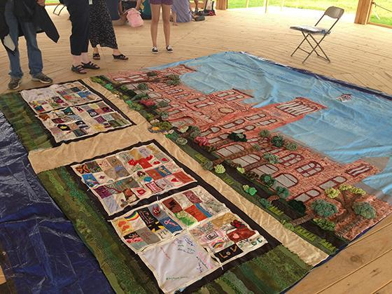 People standing around quilt panel with a design of the Smithsonian Castle on the upper half and sma