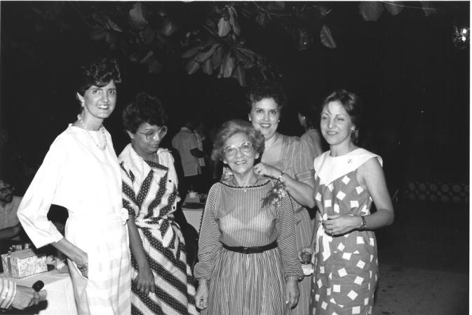 Adela Gómez standing in the center of a group of women outdoors underneath a tree.