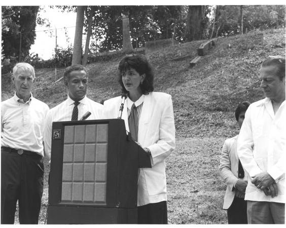 Elena Lombardo stand at a podium outdoors giving a presentation. She surrounded by three men also on