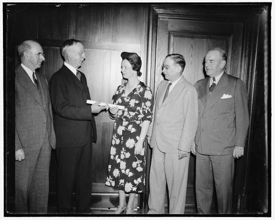 A group of men present an award to Lucile Mann and her husband in the form of a rolled-up scroll.